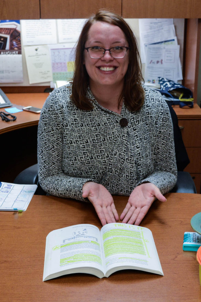 "Photo: Associate Professor of Chemistry Kelli Kazmier points to the page in ""The Biological Basis of Neuropharmacology"" where she had her ""this is it"" moment, realizing she wanted to pursue a career in biochemistry. (Hannah Kwapisz/Collegian)"