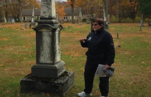 Hillsdale College Archivist Linda Moore stands with the grave of Spencer J. Fowler, a professor of mathematics and natural philosophy at Hillsdale during the 1850s, during a past Halloween tour of Oak Grove Cemetery. Linda Moore | Courtesy