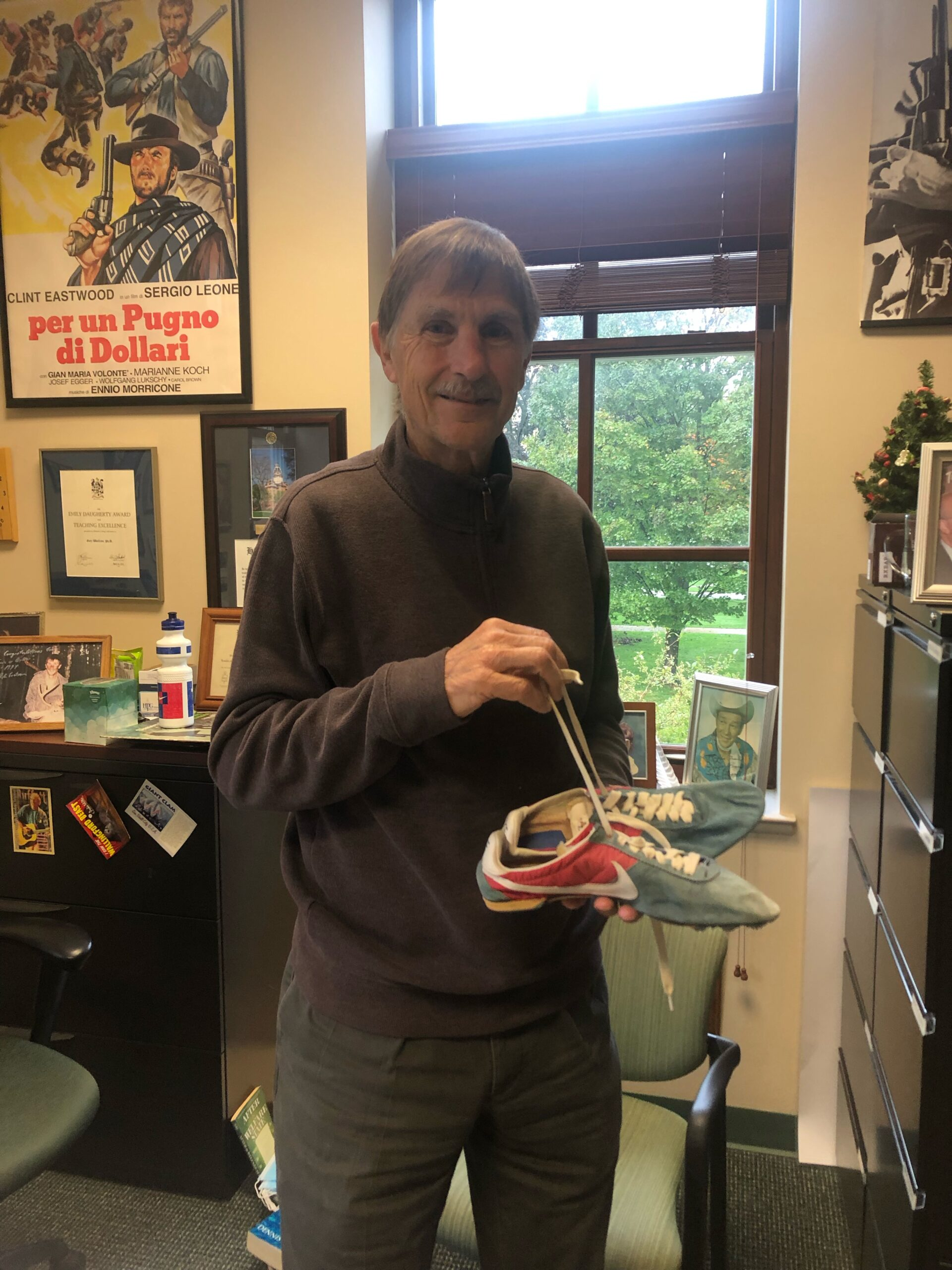 Gary Wolfram holds the shoes of record-breaking runner Henry Rono. Collegian   Aubrey Gulick