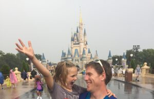 Michael Clark and his daughter smile during a rainy day at Disney World. Courtesy | Michael Clark